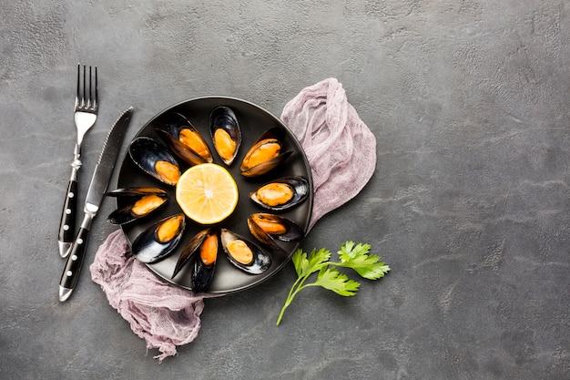 Flacher teller mit gekochten muscheln und besteck