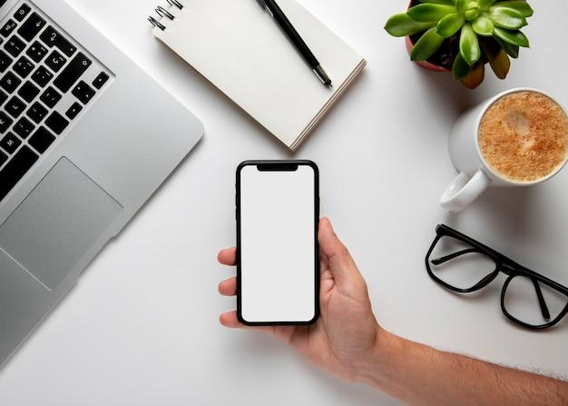 Flacher tisch mit telefon in der hand