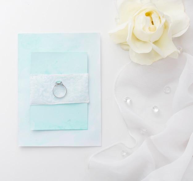 Flacher verlobungsring auf hochzeitskarte legen