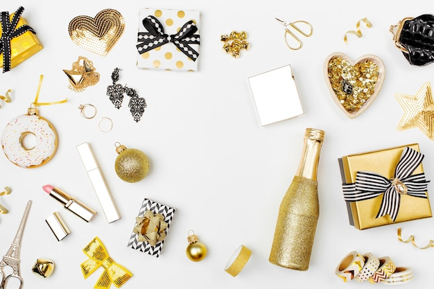 Flacher weihnachts- oder partyhintergrund mit geschenkboxen, ananas, champagnerflasche, schleifen, dekorationen und in goldfarben. flache lage, ansicht von oben