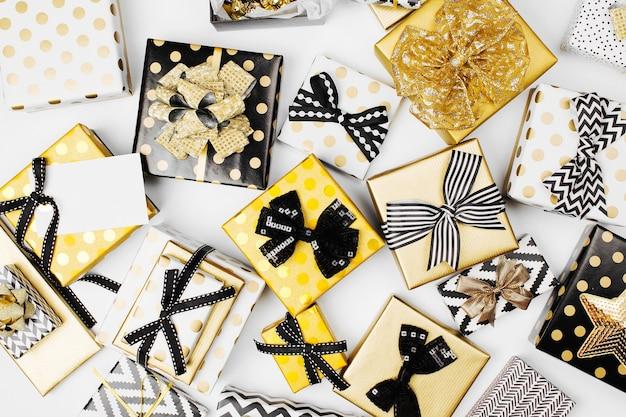 Flacher weihnachts- oder partyhintergrund mit geschenkboxen, bändern, dekorationen in gold und schwarz. flache lage, ansicht von oben