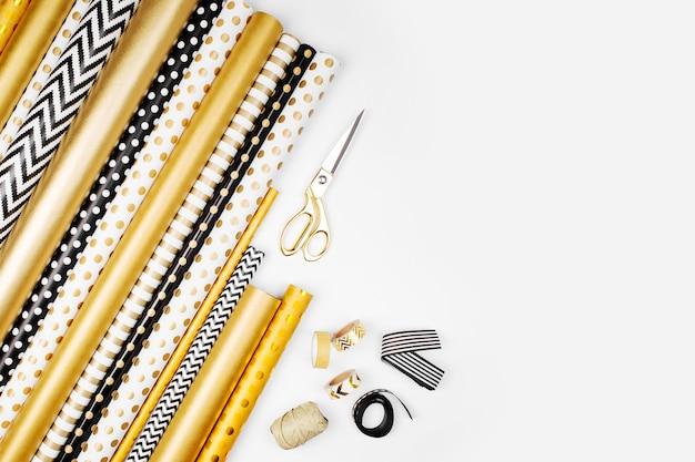 Flacher weihnachts- oder partyhintergrund mit geschenkboxen, bändern, schleifen, dekorationen und geschenkpapier in den farben gold und schwarz. flache lage, ansicht von oben