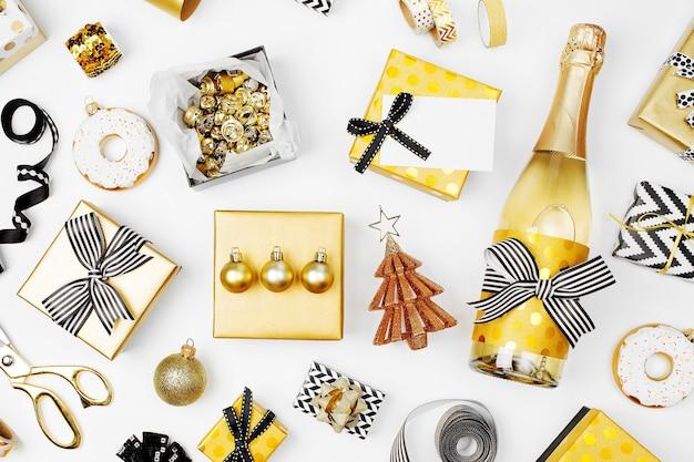 Flacher weihnachts- oder partyhintergrund mit geschenkboxen, champagnerflasche, schleifen, dekorationen und geschenkpapier in den farben gold und schwarz. flache lage, ansicht von oben