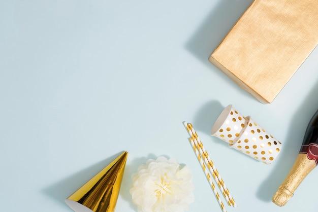 Flacher weihnachts- oder partyhintergrund mit geschenkboxen, champagnerflasche, schleifen, dekorationen und geschenkpapier in gold. flache lage, ansicht von oben