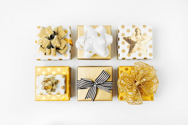 Flacher weihnachts- oder partyhintergrund mit geschenkboxen und dekorationen in goldfarben. flache lage, ansicht von oben