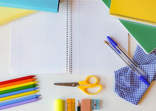 Flacher, weißer schreibtisch und farbenfrohes schulmaterial