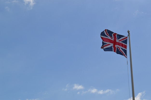 Flacher winkelschuss der flagge von großbritannien auf einer stange unter dem bewölkten himmel