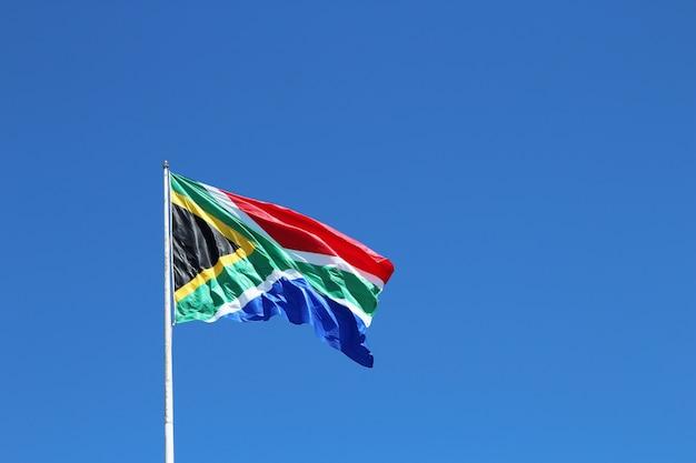 Flacher winkelschuss der südafrikanischen flagge im wind unter dem klaren blauen himmel