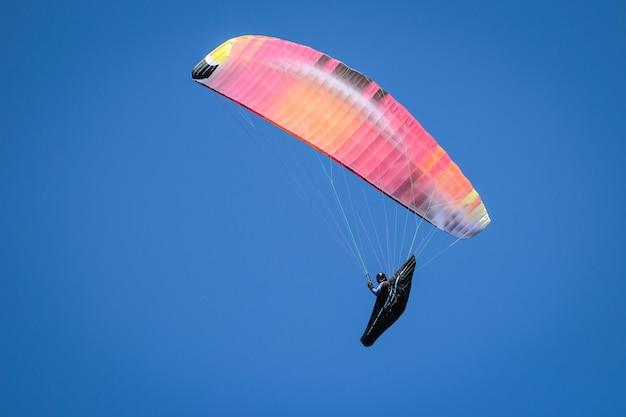 Flacher winkelschuss einer person, die an einem sonnigen tag unter dem hellen himmel paragliding ist
