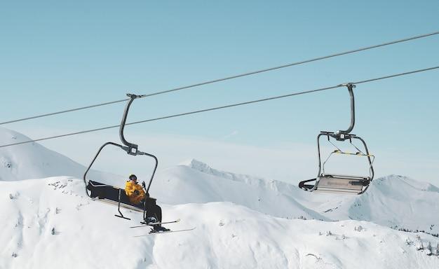 Flacher winkelschuss einer person, die auf einer seilbahn in einem schneebedeckten berg sitzt