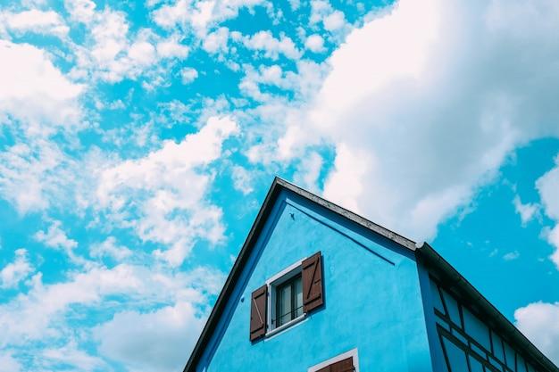 Flacher winkelschuss eines blauen bauernhofgebäudes, das den bewölkten himmel berührt