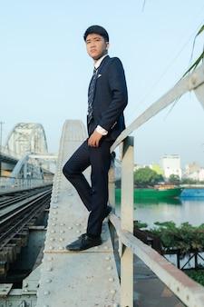 Flacher winkelschuss eines jungen asiatischen mannes in einem anzug, der sich auf brückengeländer stützt