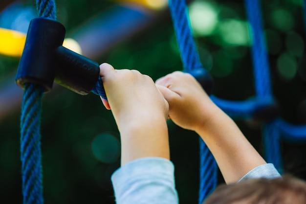 Flacher winkelschuss eines kindes, das an einem blauen kletterspielzeug auf dem spielplatz eines parks festhält