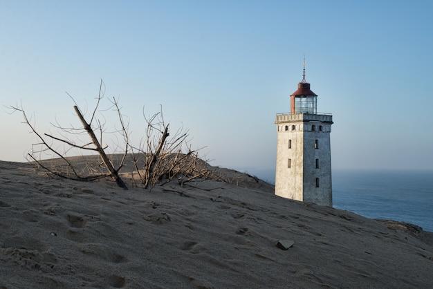 Flacher winkelschuss eines leuchtturms, der auf einem hügel während des sonnenuntergangs steht
