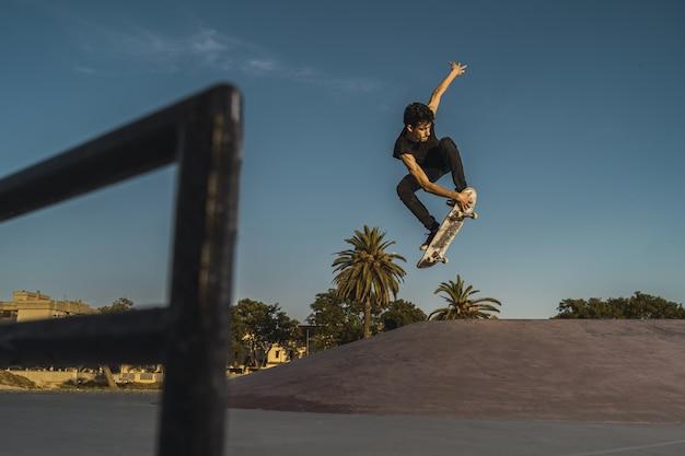 Flacher winkelschuss eines mannes, der in einem leeren skatepark mit bäumen und einem himmel skateboardt