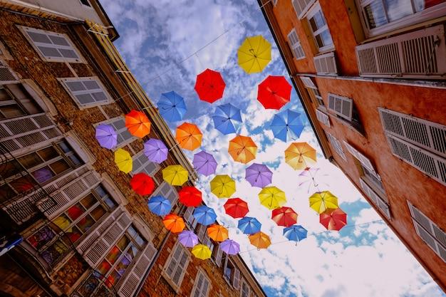 Flacher winkelschuss von bunten regenschirmen, die in der mitte von gebäuden mit bewölktem himmel hängen