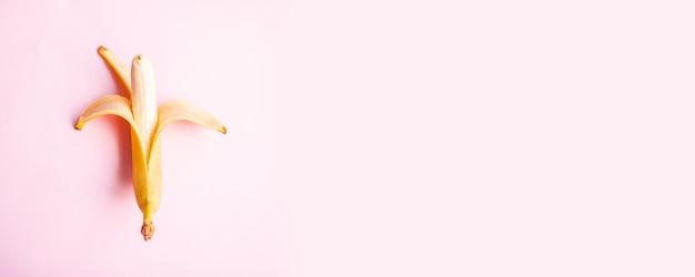 Flacher zusammensetzungsbonbon zwei bananen auf rosa hintergrund mit kopienraum für ihren text. ansicht von oben. flach liegen
