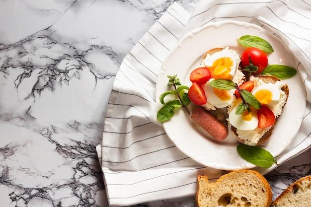 Flaches brot mit hartgekochten eiern, tomaten und würstchen