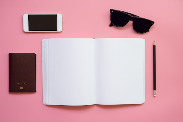 Flaches design des arbeitsplatzes schreibtisch mit leerem notizbuchbleistiftsonnenbrillehandy und -pass auf weinlesepastellfarbhintergrund. reisekonzept