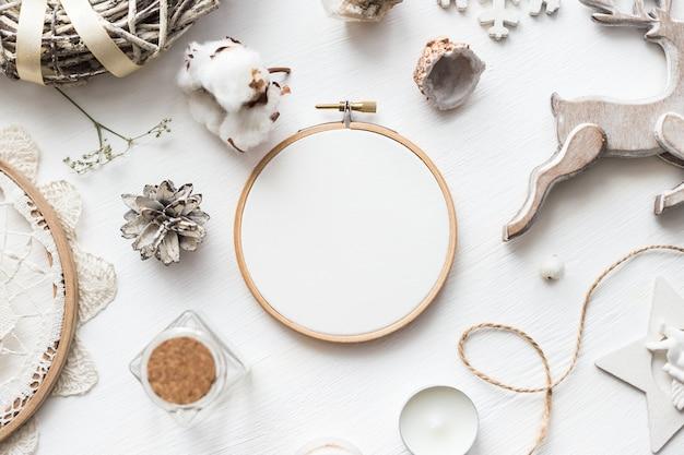 Flaches draufsichtfoto eines modells mit stickrahmen und weihnachtsde. stilvolle feminine layout-komposition für das neue jahr.