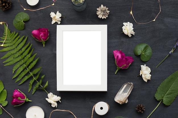Flaches draufsichtmodell eines rahmens auf schwarzem hintergrund mit wilden blumen. schönes trendiges layout-foto.