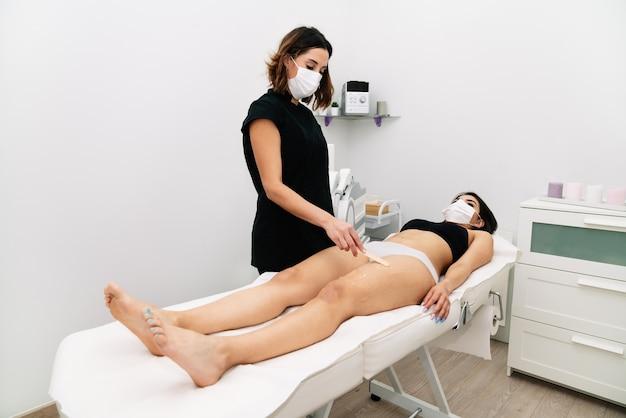 Flaches foto einer kosmetikerin, die eine frau auf ihrem oberschenkel mit einem enthaarungswachs auf einer trage in einer klinik mit einer maske im gesicht aufgrund der 2020er covid-19-coronavirus-pandemie behandelt