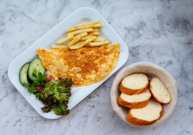 Flaches frühstück mit omelette, gemüse und brotkorb.