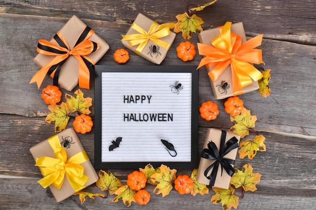 Flaches glückliches halloween. festliche komposition für halloween auf einem hölzernen hintergrund mit kürbissen und geschenken.
