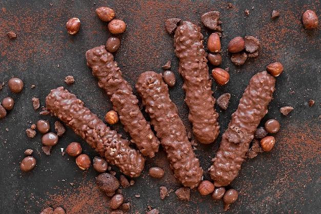 Flaches kreatives schokoladensortiment auf dunklem hintergrund