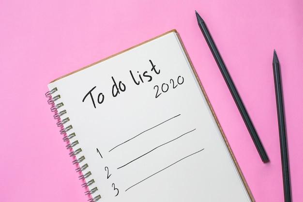 Flaches lage neues jahr, zum der liste auf leerem notizbuch zu tun, konzept des planungswunsches 2020