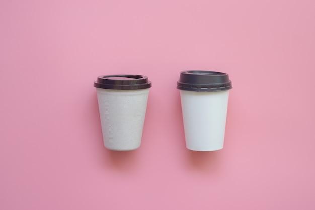 Flaches lagedesign der art zwei der heißen kaffeetasse auf rosa pastell.