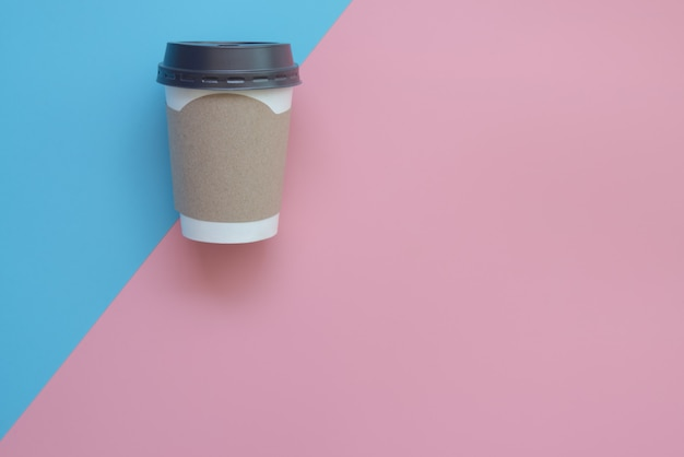 Flaches lagedesign der heißen kaffeetasse mit leerer pappe für ihre marke auf rosa und blauem pastell.