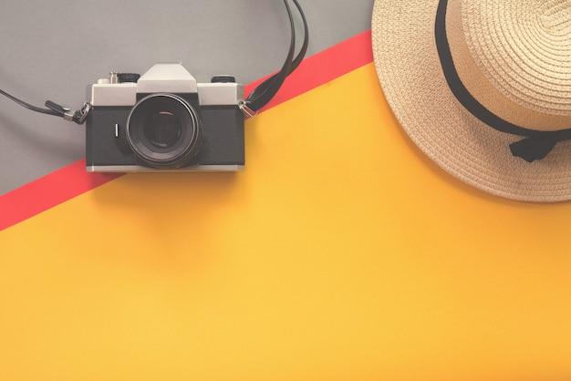 Flaches lagedesign des arbeitsschreibtischs mit alter kamera und strohhut