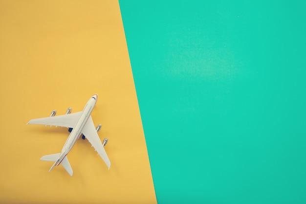 Flaches lagedesign des reisekonzeptes mit flugzeug auf grünem und gelbem hintergrund