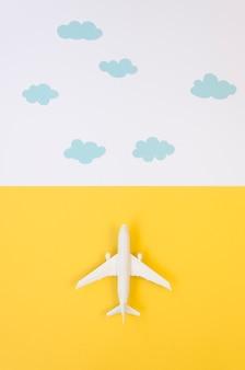 Flaches lageflugzeugspielzeug mit wolken