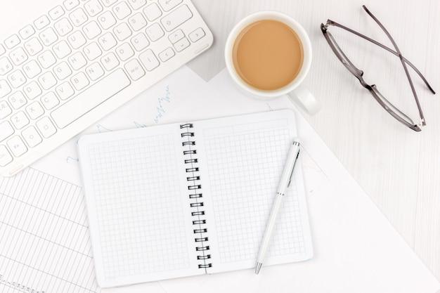 Flaches lagefoto des weißen schreibtischs mit laptop, smartphone, brillen, notizbuch und stift mit kopienraumhintergrund. attrappe, lehrmodell, simulation