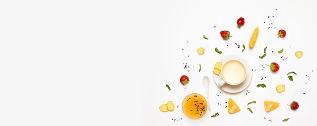 Flaches lagekonzept einer tasse ingwertee, zuckerwürfel, erdbeeren, ingwerstücke, orange und tadellose blätter