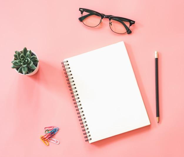 Flaches lagemodeldesign des arbeitsplatzschreibtischs mit leerem notizbuch, smartphone, kaffee, briefpapier auf rosa pastellfarbe mit kopienraum