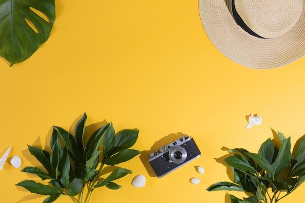 Flaches lagendesign des gelben hintergrundes mit laptop, fotokamera, tropischem blatt der grünen palme und blumen, draufsicht. sommerhintergrund, ferien und feiertage, reise- und reiseplanungskonzept