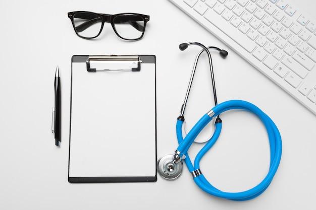 Flaches lagendesign des stethoskops und der leeren klemmbrettauflage mit für medizinisches konzept.