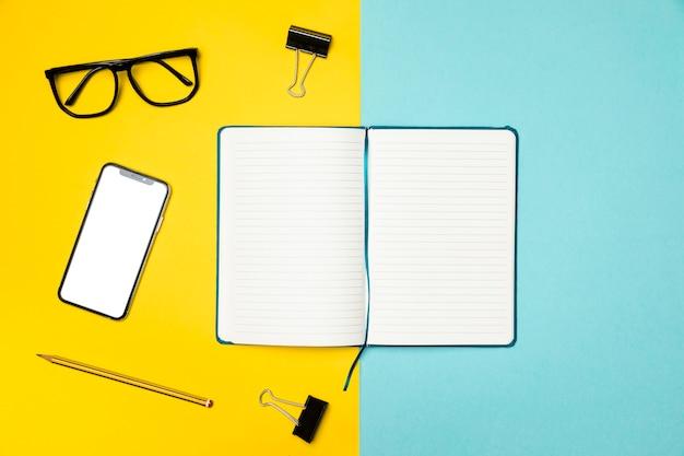 Flaches lageschreibtischkonzept mit offenem notizbuch