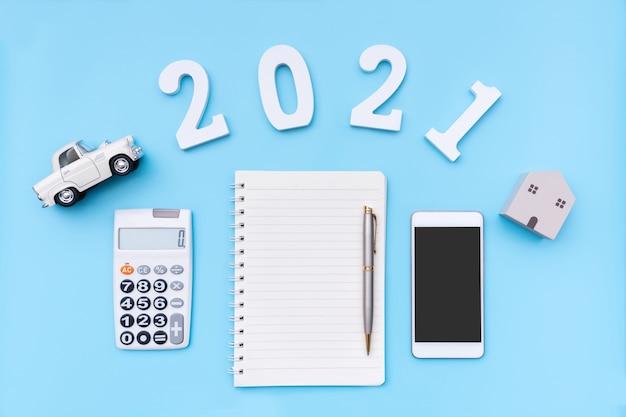 Flaches laien-notizbuchrechner-smartphone-modellauto und haus auf blauem hintergrund neujahrsplanungskonzept kopieren sie die draufsicht des raums