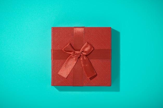 Flaches laienfoto der roten geschenkbox auf blauem tisch