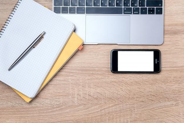 Flaches laienfoto des hölzernen schreibtischs mit laptop, stift und notizbuch mit hintergrund des kopierraums.