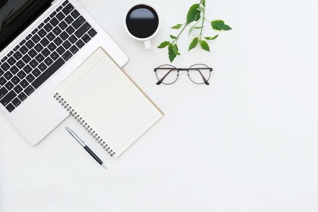 Flaches laienfoto des schreibtisches mit laptopkopienraumhintergrund