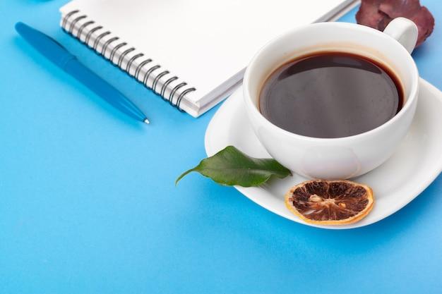 Flaches laienfoto mit notizbuch, kaffeetasse auf blauem hintergrund
