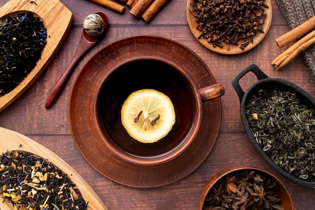 Flaches laiengesteck mit einer tasse tee und kräutern