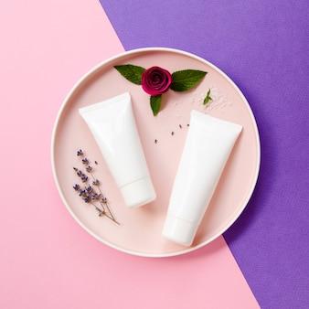 Flaches laiengesteck mit sahneflaschen und rose