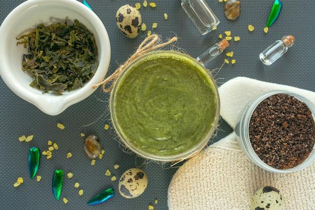 Flaches laienkörper-kosmetikkonzept. körperpeeling natürliche gesichts- und körpermaske oder -peeling mit kaffee, meersalz, algen, wachtelei und natürlichem öl