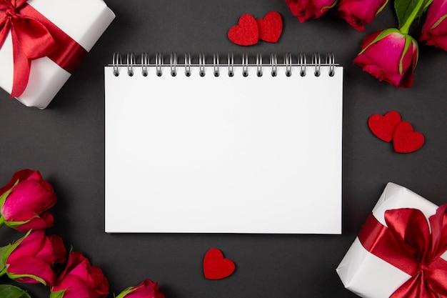 Flaches laienkonzept von valentinstag, jahrestag, muttertag und geburtstag mit papierspiralheft und geschenkboxen mit rotem band, herzen, rosen auf dunkelheit.